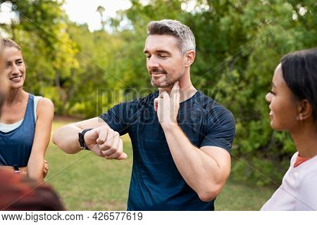 Mature tired man checking pulse after workout. Handsome middle aged man standing with group of friends measuring heart rate pulse on his neck and looking sport watch. Guy times the pulsations at park.
