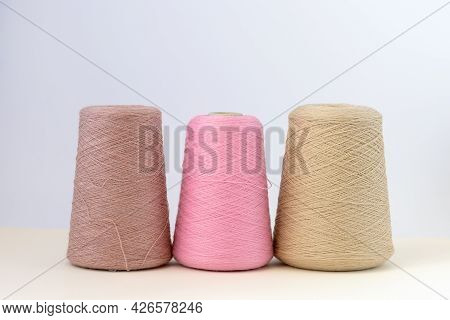 Pastel Color Bobbins Of Wool Yarn For Hand And Machine Knitting On A White Background