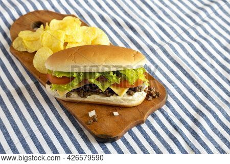 Homemade Chopped Beef Sandwich With Potato Chips On A Rustic Wooden Board, Side View. Space For Text