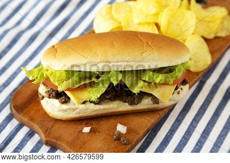 Homemade Chopped Beef Sandwich With Potato Chips On A Rustic Wooden Board, Low Angle View. Close-up.