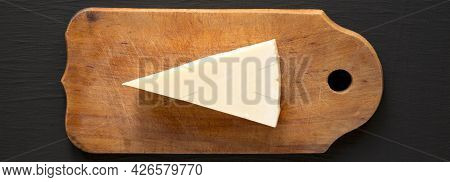 Pecorino Romano Cheese On A Rustic Wooden Board On A Black Surface, Top View. Flat Lay, Overhead, Fr