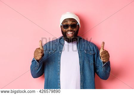 Satisfied African-american Hipster Guy In Beanie And Sunglasses Showing Thumbs-up, Approve And Prais