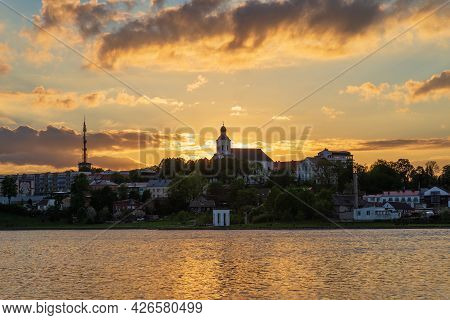 Town Sea Coast At The Sunset Evening.sun Rays Passing Through Storm Clouds Over The Lake Bay Town. U