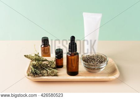 Cannabis Oil Extract In Droplet Bottles And Tube Of Face Moisturizer, Dried Hemp Leaves And Seeds. M