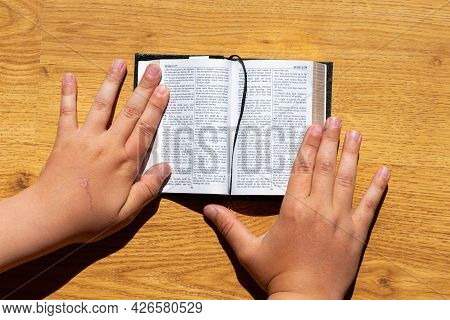 Childs Hands Hold A Bible Leaning On A Wooden Table. Small Book Holy Bible.kid Reading From The Holy