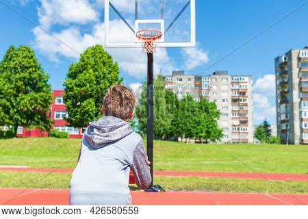 Boy Preparing For Basketball Shooting At Playground.boy Performs Shot At Basketball Game On The Play