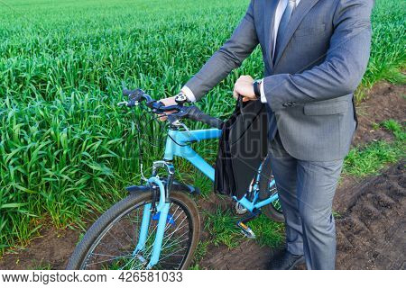 Businessman with a bicycle looking at his wristwatch in a green grass field - business concept for freedom, vacation or freelance. Beautiful spring nature.