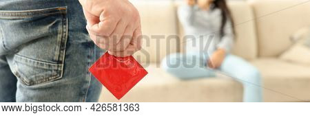Man Is Holding Condom In Front Of Woman Sitting
