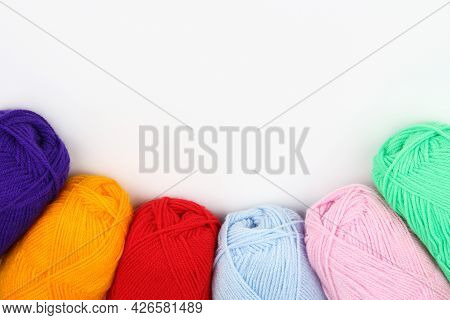 A Lot Of Multi-colored Wool Balls Of Knitted Yarn Lie At The Bottom In An Arc Close-up On A White Ba