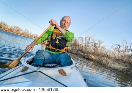 senior male is paddling expedition canoe, early spring scenery on a lake in northern Colorado, POV from a bow with boat leaning during turn