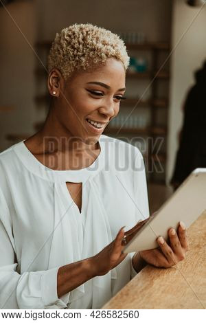 Black businesswoman using a digital tablet in a cafe