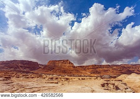 Gorgeous flying cumulus clouds. Ancient mountains and deserts around the Dead Sea. Hot afternoon in the Judean Desert.