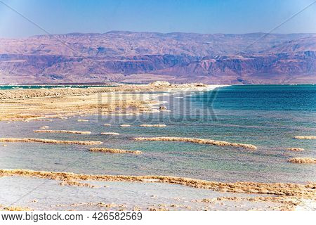 Israeli coast of the Dead Sea. The evaporated salt forms intricate patterns on the surface of the water. Windy spring day. The pink mountains of the Jordanian coast