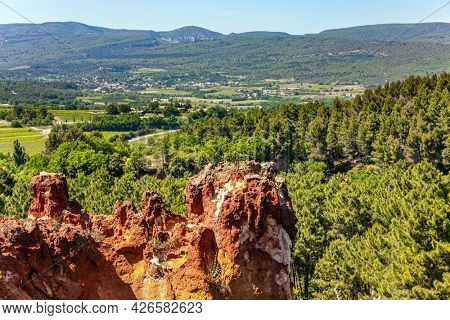Bizarre ocher rocks, where the pigment quarry used to be. The rocks are covered with forest. The village of Roussillon. Travel to fabulous sunny Provence. France