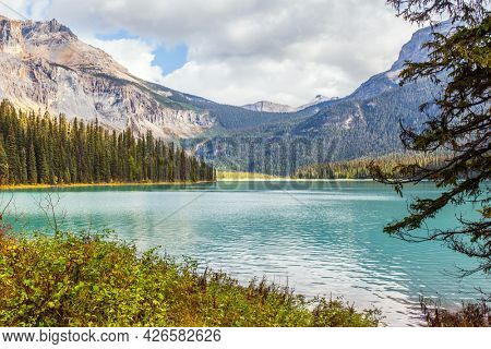 Sunny cold day in the Rocky Mountains. Magnificent Emerald Lake. Coniferous forest and mountain peaks surround the lake with azure water. The concept of active, ecological and photo tourism