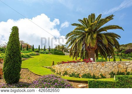 Haifa, Israel. Pilgrimage center and popular tourist destination. Gorgeous colorful gardens, flower beds and green lawns attract pilgrims and tourists. Sunny day by the sea
