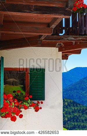 Lovely mountain chalet. Corner of a house with a window with shutters. Dolomites on a sunny autumn day. Europe, Val de Funes, sunny bright day