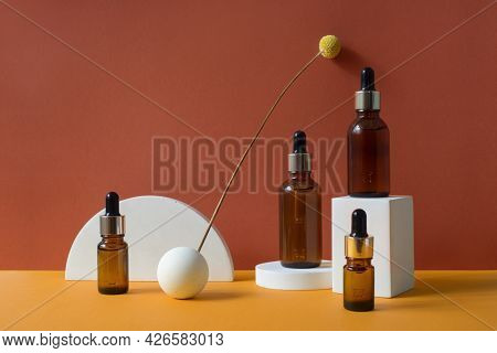 Amber Glass Dropper Bottles With Metallic Lid On The White Podiums. Orange And Terracotta Background