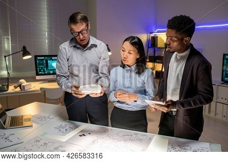 Chief engineer showing 3D model to young multi-ethnic designers and telling concept of new car model in office