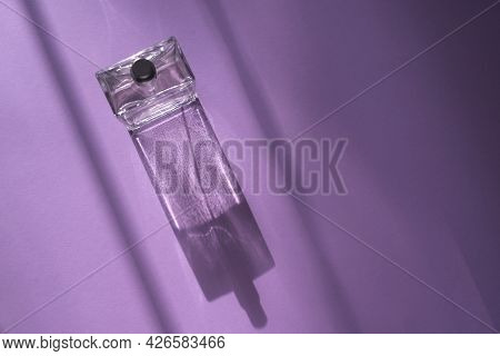 A Bottle Of Perfume On An Lilac Background With Natural Light And Geometric Diagonal Shadows. Beauti