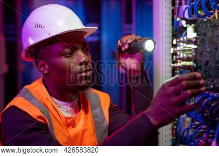 Serious young African-American server repairman in hardhat using flashlight while checking server rack