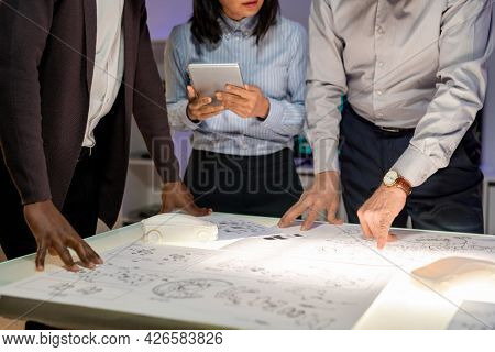 Group of multi-ethnic engineers standing at table with sketches and discussing innovative solutions for new car