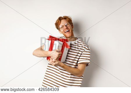 Valentines Day And Holidays Concept. Happy Redhead Man Hugging His Gift Box And Thanking, Looking At