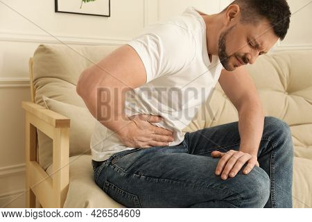 Man Suffering From Pain In Lower Right Abdomen On Sofa At Home. Acute Appendicitis