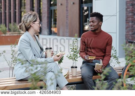 Two young multiracial co-workers having lunch on bench outdoors