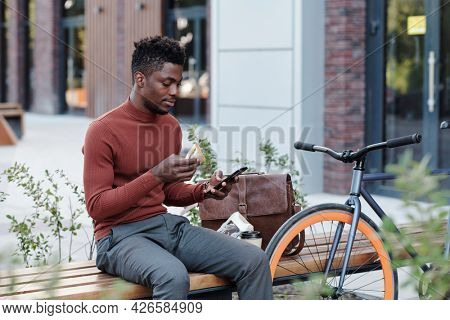 Serious African white collar worker eating sandwich and using smartphone