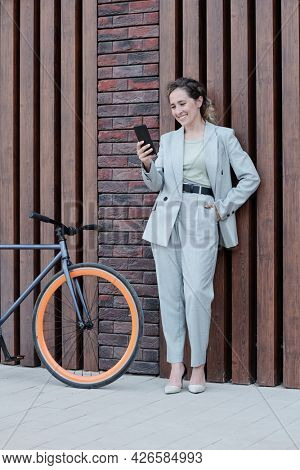 Well-dressed businesswoman with smartphone talking through video chat outdoors