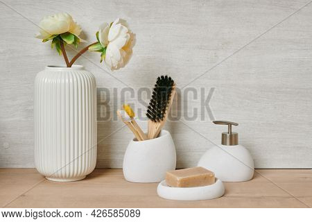 Group of bodycare items against white wall in bathroom