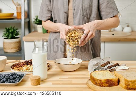 Young female in casualwear putting muesli into bowl while making breakfast