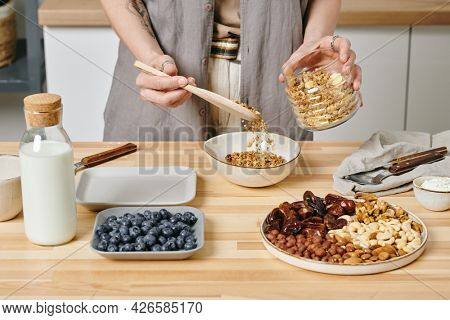 Hands of female putting muesli into bowl while preparing breakfast