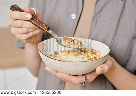 Hands of female holding bowl with muesli and spoon
