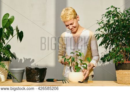 Smiling blond woman looking at green plant in white flowerpot