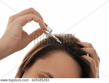 Mature Woman Applying Oil Onto Hair On White Background, Closeup. Baldness Problem