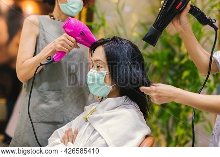 Woman In Medical Mask Getting Her Hair Dried At The Hair Salon