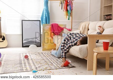 Young Man Sleeping On Sofa In Messy Room After Party