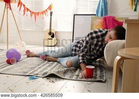 Young Man Sleeping Near Sofa In Messy Room After Party