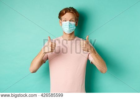 Covid-19, Pandemic And Lifestyle Concept. Cheerful Redhead Guy In Medical Mask Showing Thumbs Up In