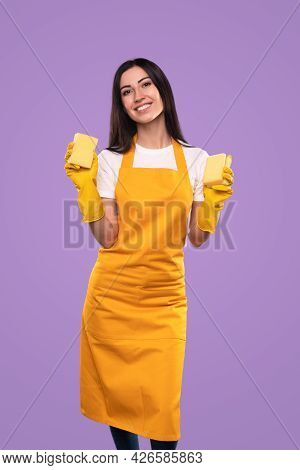 Confident Positive Young Woman In Yellow Apron And Gloves Demonstrating Sponges While Preparing For