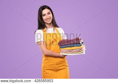 Optimistic Young Female Housekeeper In Yellow Apron With Stack Of Clean Washed Clothes Smiling And L