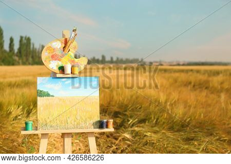 Wooden Easel With Beautiful Picture And Painting Equipment In Field. Space For Text
