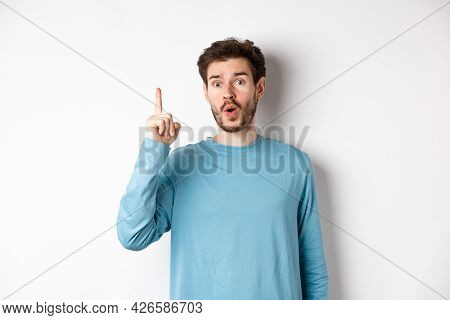 Image Of Excited Handsome Man Pitching An Idea, Raising Finger And Saying Eureka, Standing Over Whit