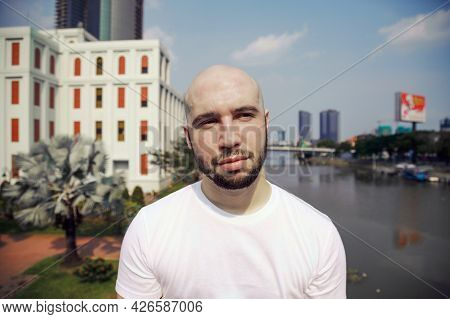 Young Handsome Man In A White T-shirt Daydreaming On A City Street. Bald Bearded Tourist Standing Ag