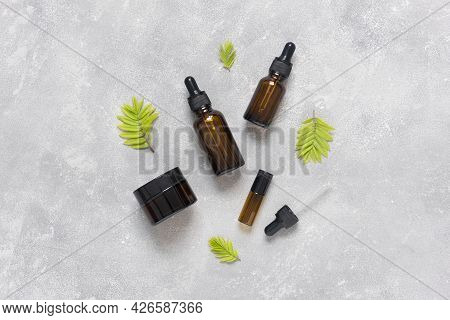 Bottles Of Dark Amber Glass With Essential Oil And Face Cream On A Gray Concrete Background. Spa Org