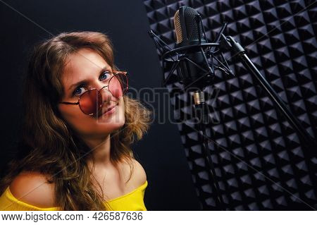 Young Woman In Red Glasses And Yellow Clothes Sings Into The Recording Studio. Musician In Recording