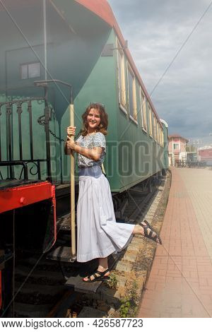 Woman Standing On The Running Board Of The Car. Holding The Handrail Of The Departing Train. Empty P