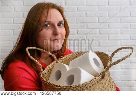 A Woman Holds Rolls Of Toilet Paper In A Large Basket, Close-up. Problems With Toilet Paper In The S